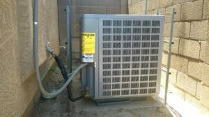 Air conditioning unit shown between a home and yard wall.